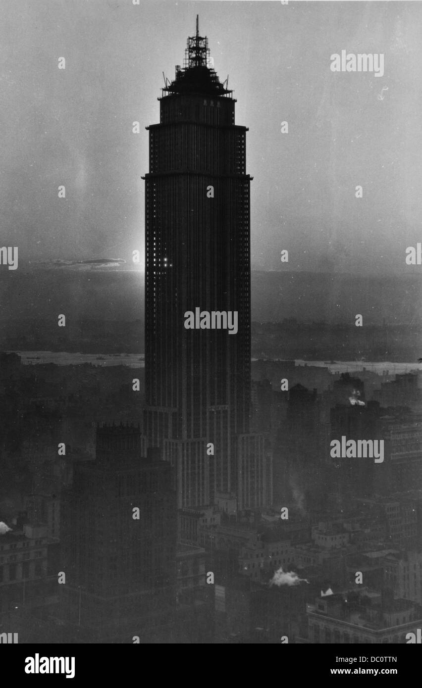1930s CONSTRUCTION NEARLY COMPLETE ON EMPIRE STATE BUILDING SUN SHINING THRU SKELETON OF STRUCTURE JUNE 1931 - Stock Image