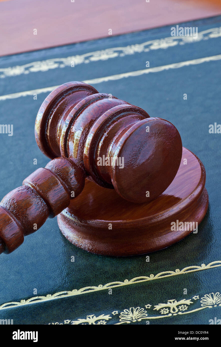 Auctioneers/Judges wooden gavel and striker block on traditional leather inlaid desk - Stock Image