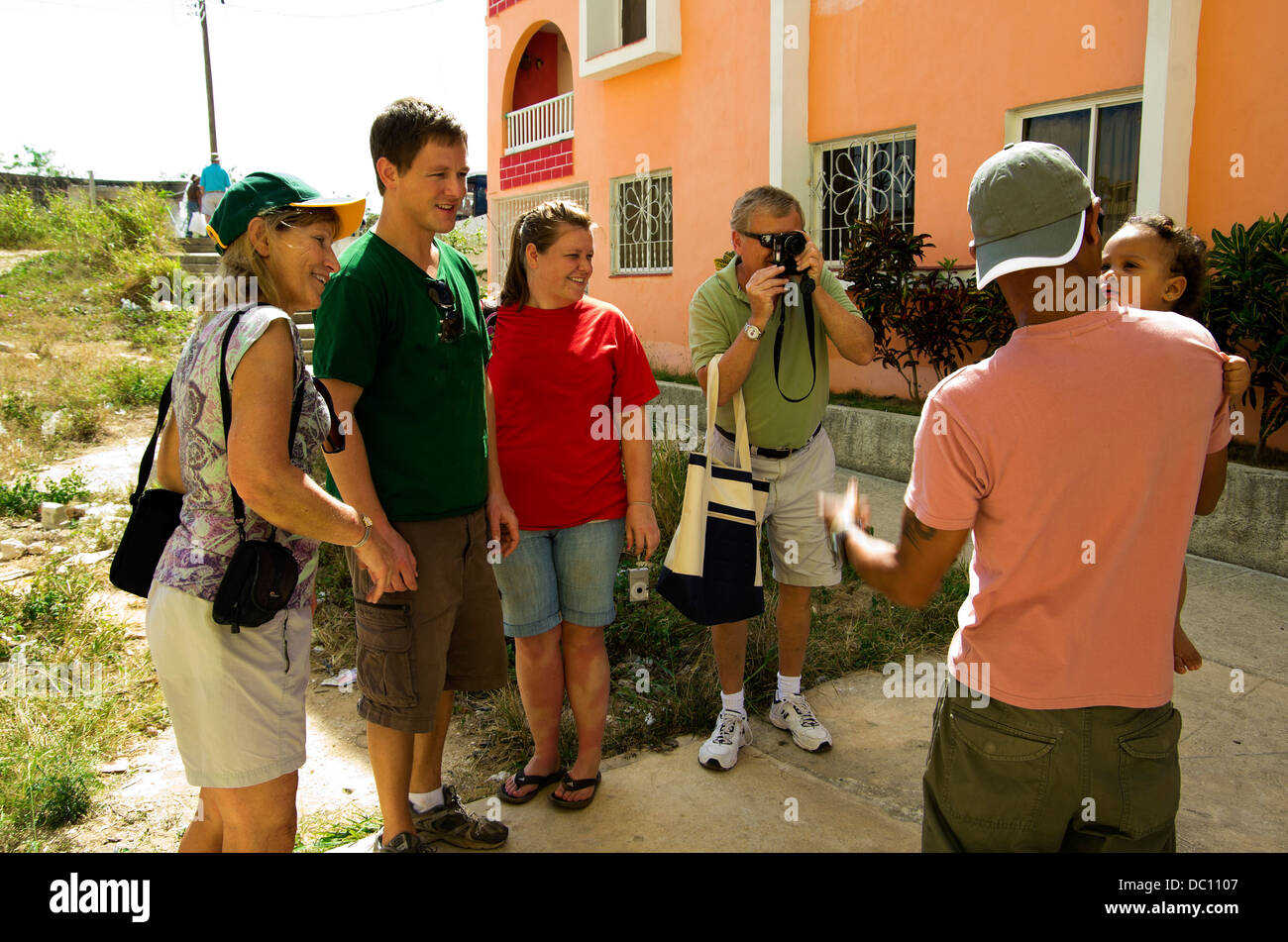 Tourist father photographs Cuban father and baby, as tourist mother, son and daughter watch. Stock Photo