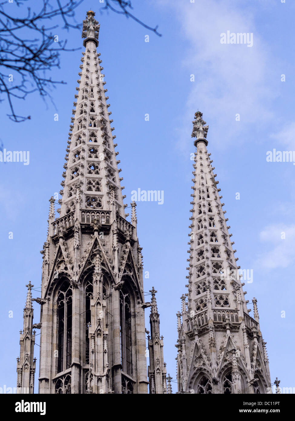 Votive Twin Spires. The bright stone of the filigreed spires of this landmark Vienna church with a blue sky. - Stock Image