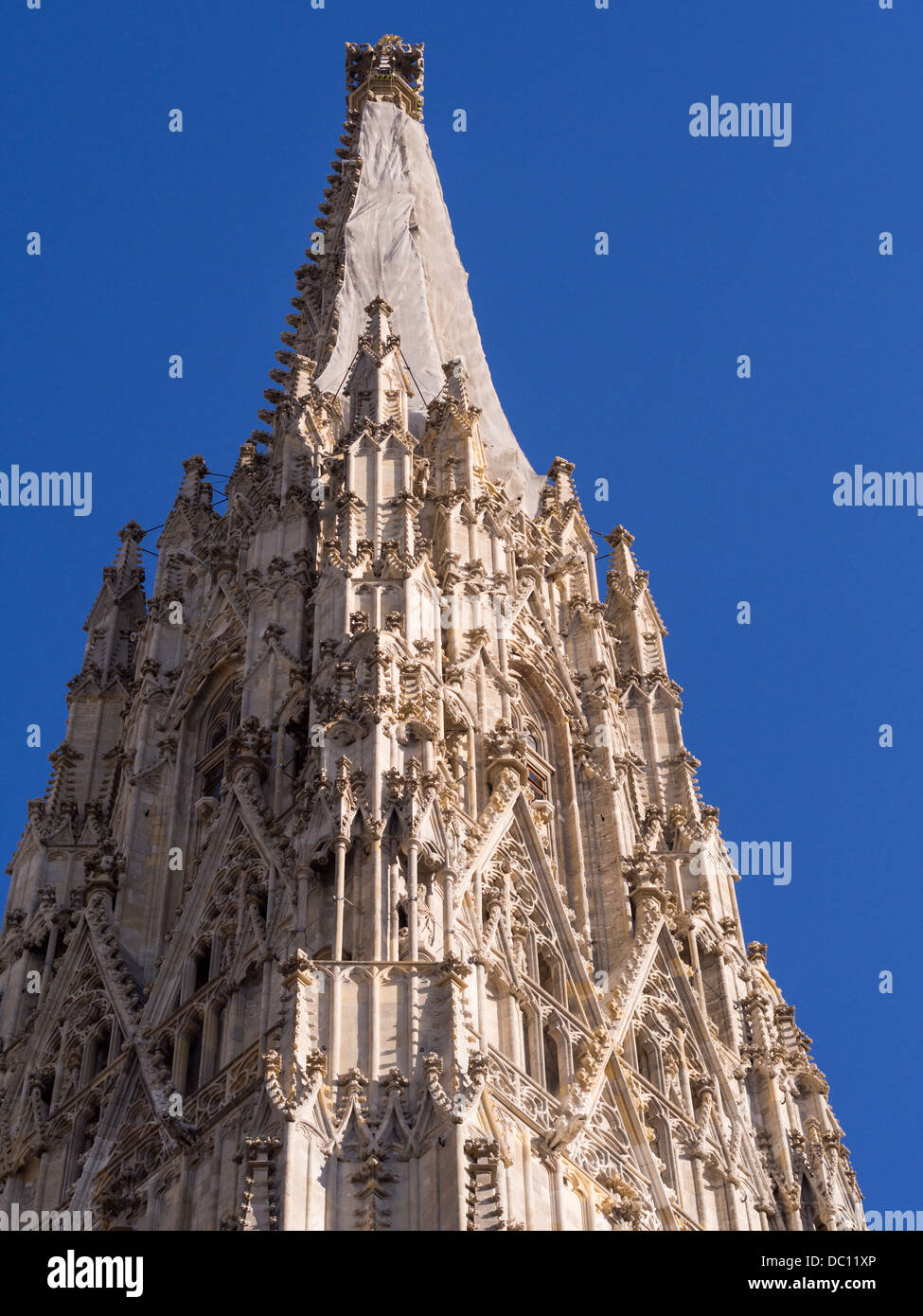 Shrouded South Spire of Stephansdom. A tarp covers the intricate stonework for restoration work at the peak of the - Stock Image