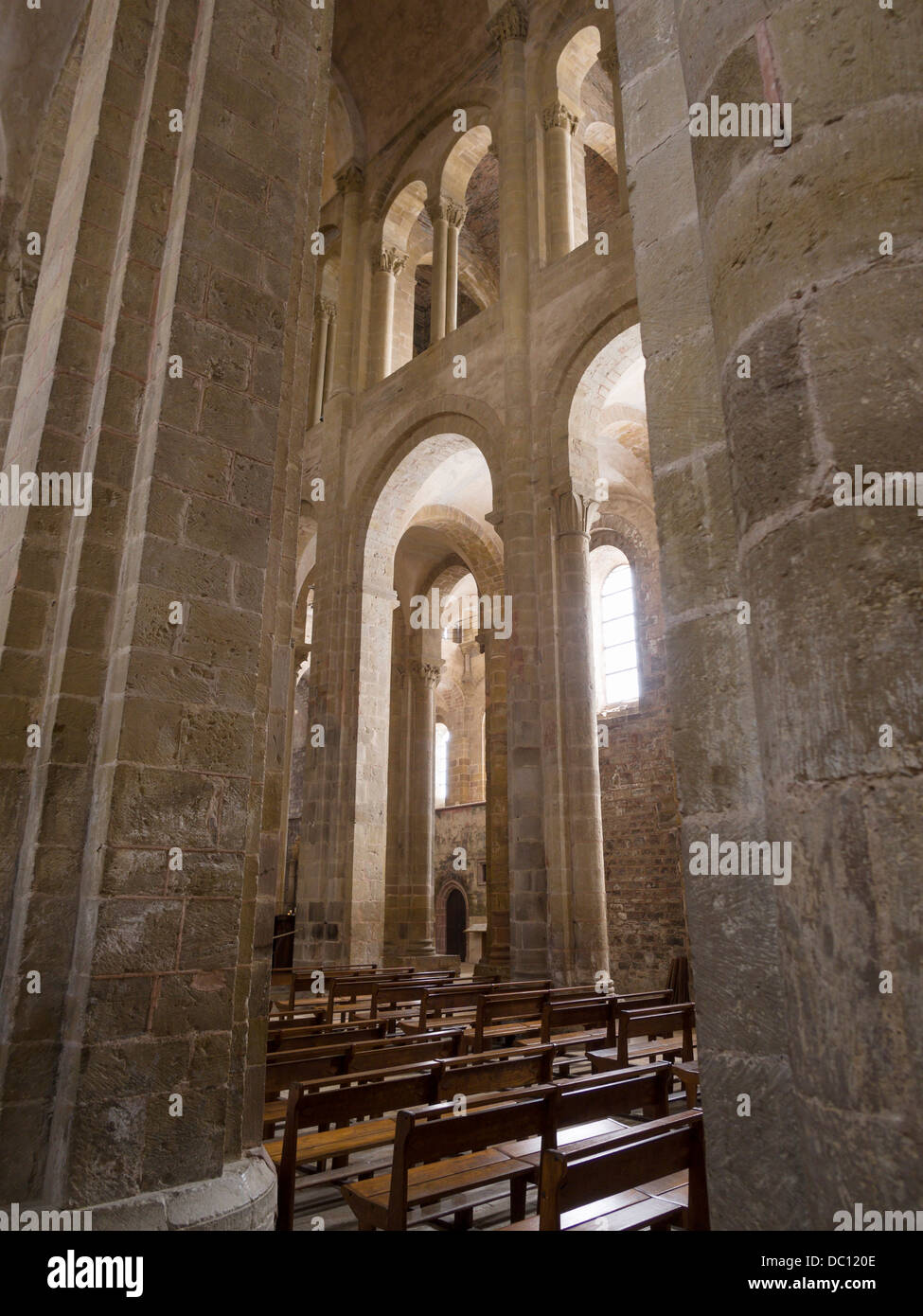 The austere interior of the Church of Saint Foy . Columns soar and the plain stonework glows in this image of St. - Stock Image