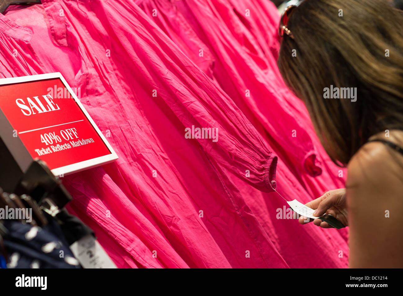 Woman bargain hunting in a clothing store. - Stock Image