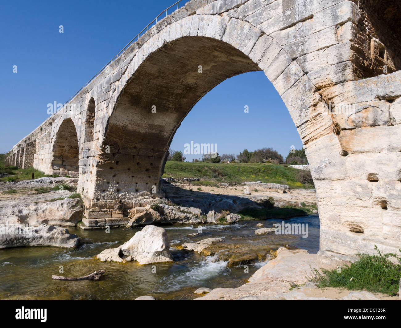 Pont Julien in Provence. The famous multi-arched stone bridge spans the Calavon and part of the ancient Roman road - Stock Image