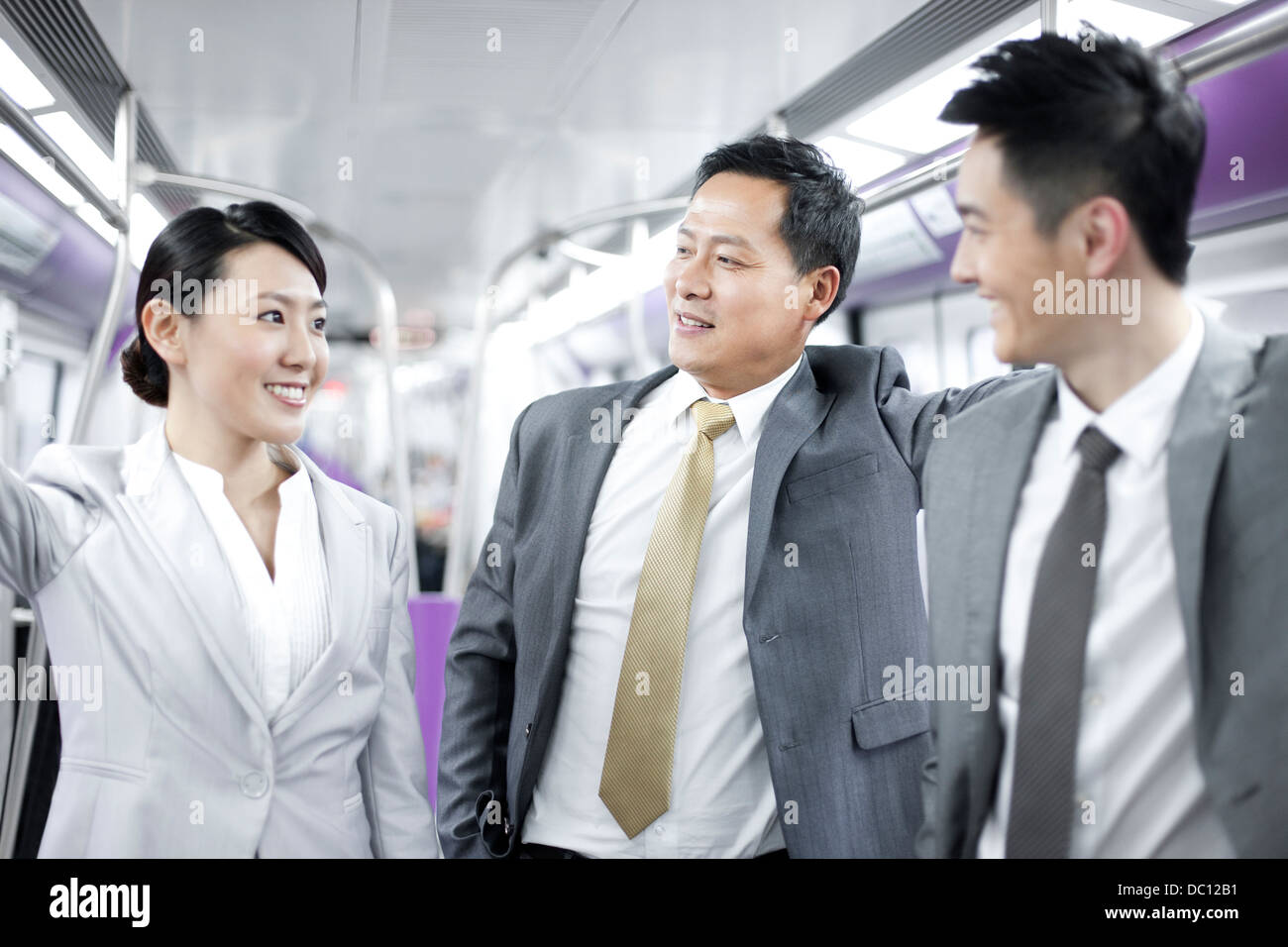 Cheerful business persons in subway train Stock Photo