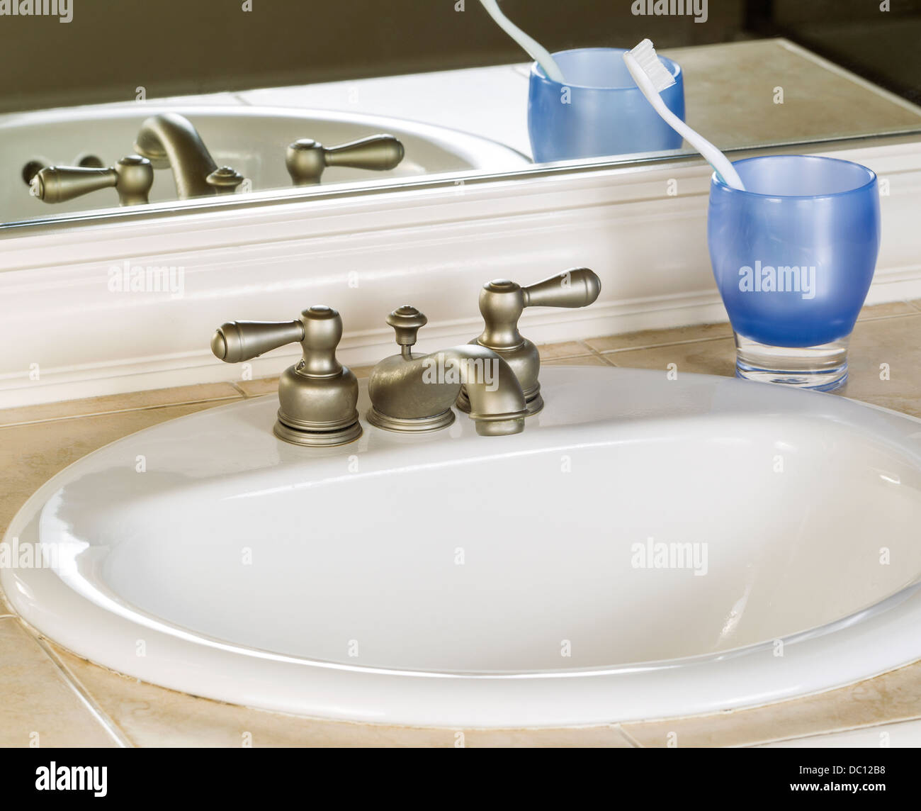 Photo of bathroom sink and faucet with blue cup, tooth brush and mirror in background - Stock Image
