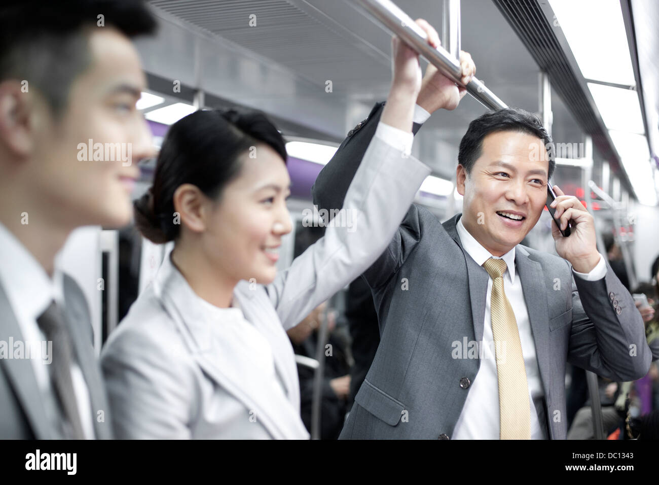 Cheerful business persons in subway train - Stock Image