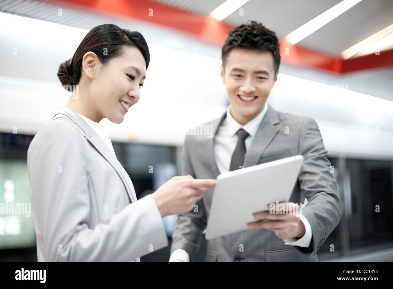 Young business partners with digital tablet on subway platform - Stock Image