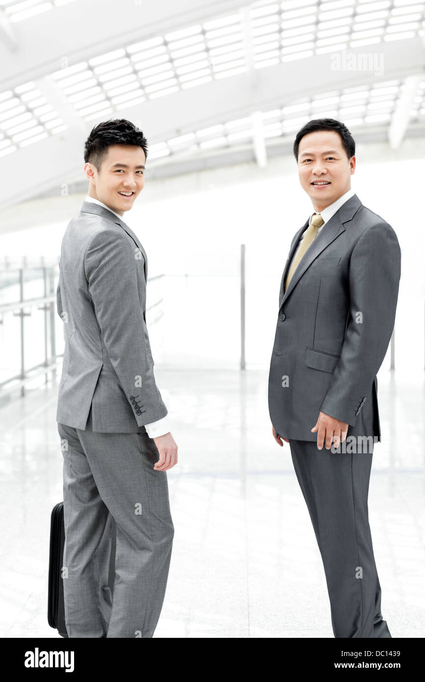 Confident business people in airport lobby - Stock Image
