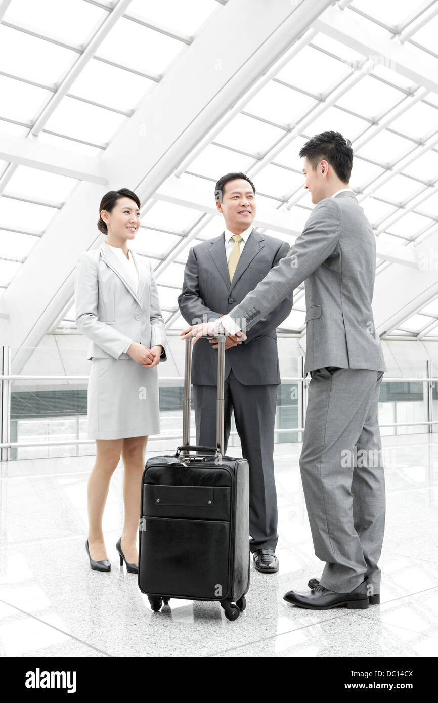 Business partners having conversation in airport lobby - Stock Image