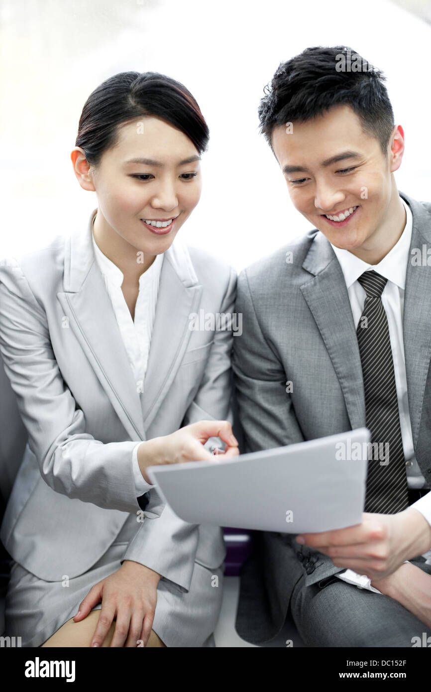 Business partners reading files in subway train - Stock Image