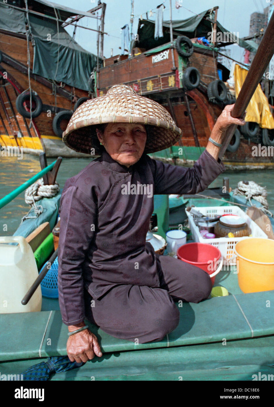 A junk woman wearing a traditional bamboo hat in Hong Kong harbour. - Stock Image