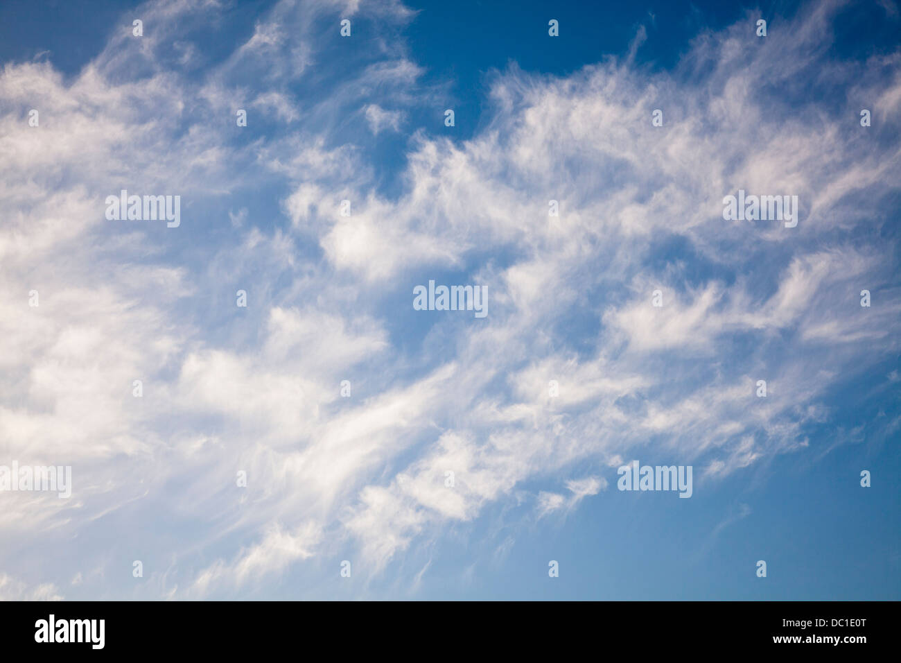 White cirrocumulus cloud in a bright blue sky on a summer's day. - Stock Image