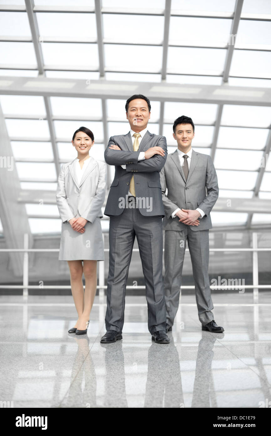 Confident Chinese business people in airport lobby - Stock Image