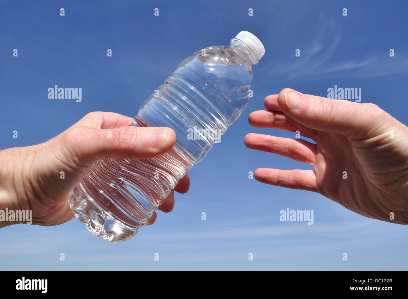 Hand Offering a Bottle of Water Against a Blue Sky - Stock Image
