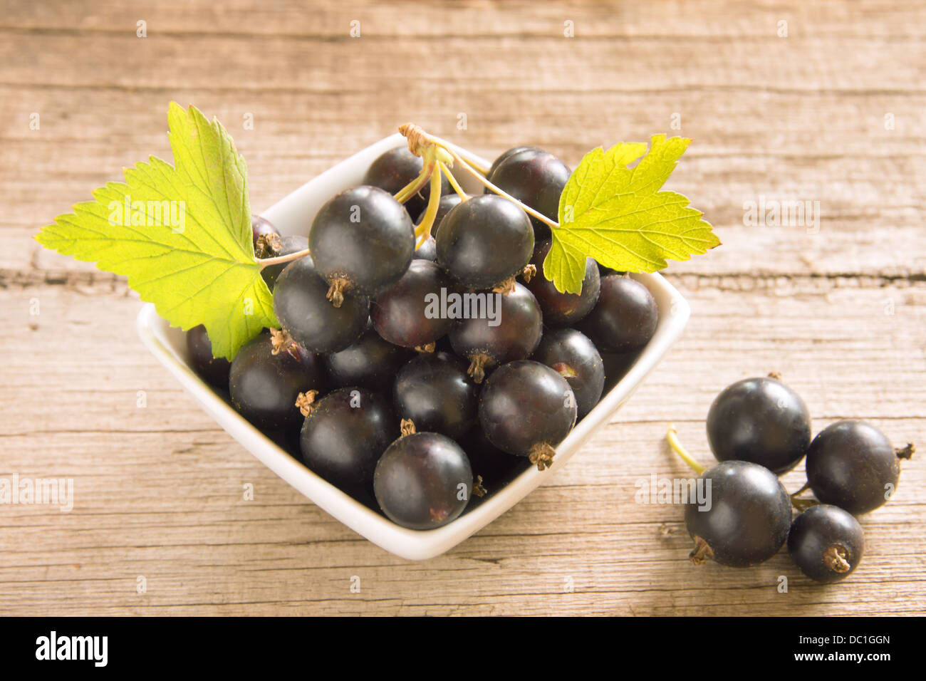 Black currant with green leaves on rustic old wooden background, horizontal, close up Stock Photo