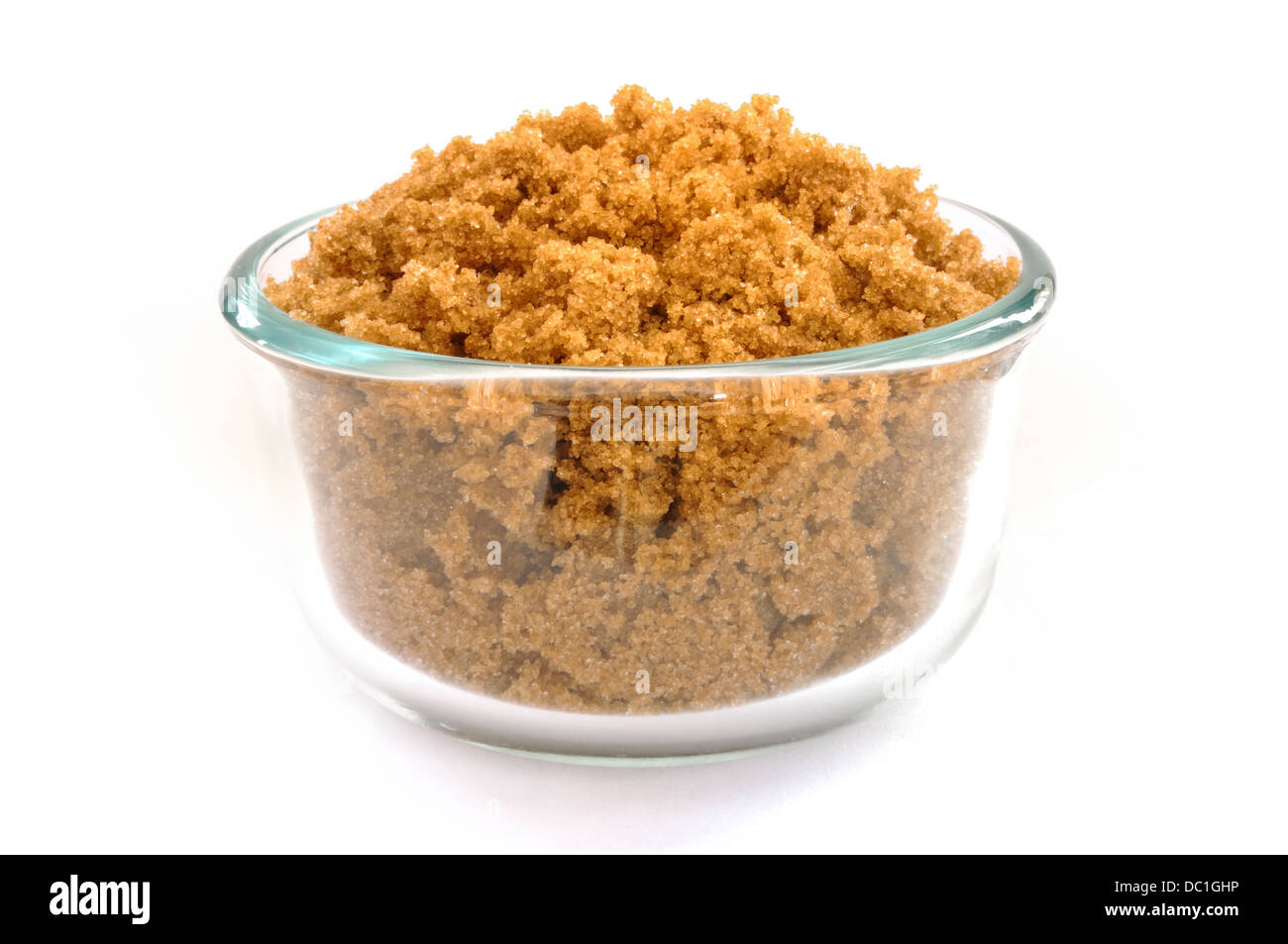 Brown Sugar in a Glass Bowl Isolated on White - Stock Image