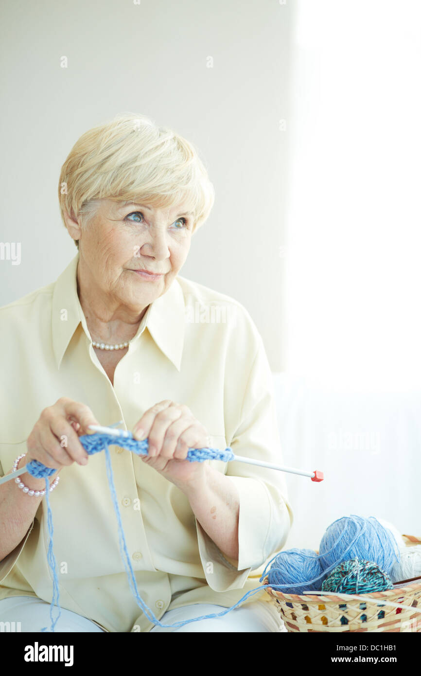 Portrait of elderly woman knitting at home - Stock Image