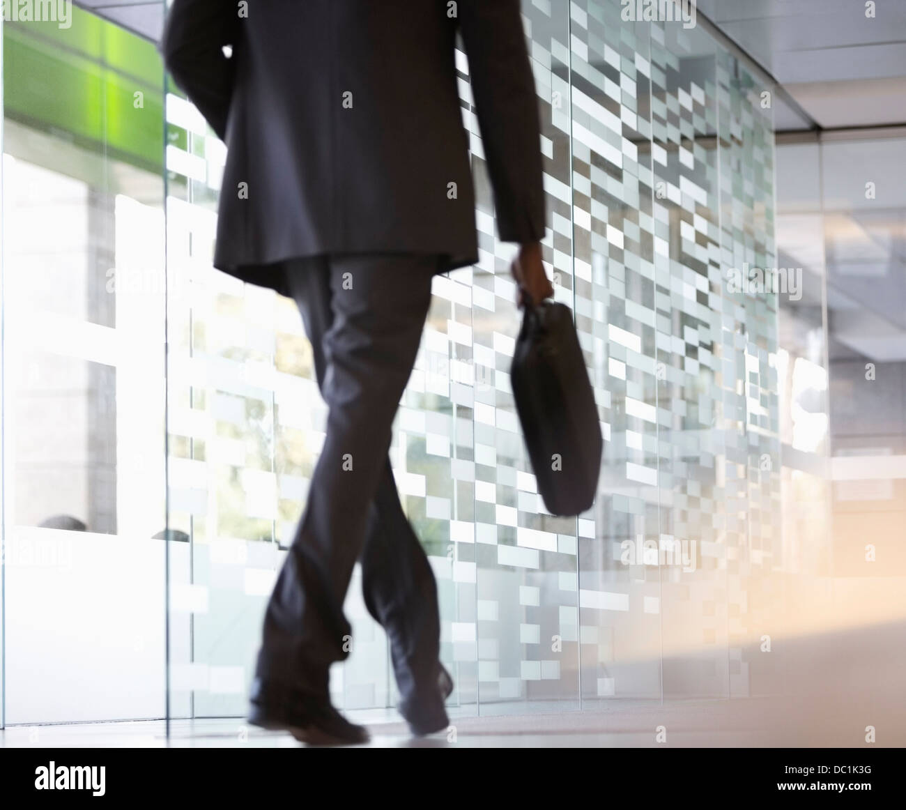 Businessman with briefcase walking in lobby - Stock Image