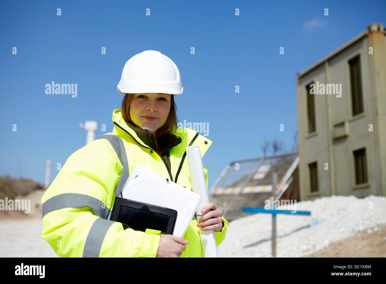 Portrait of female with blueprint and digital tablet on construction site - Stock Image