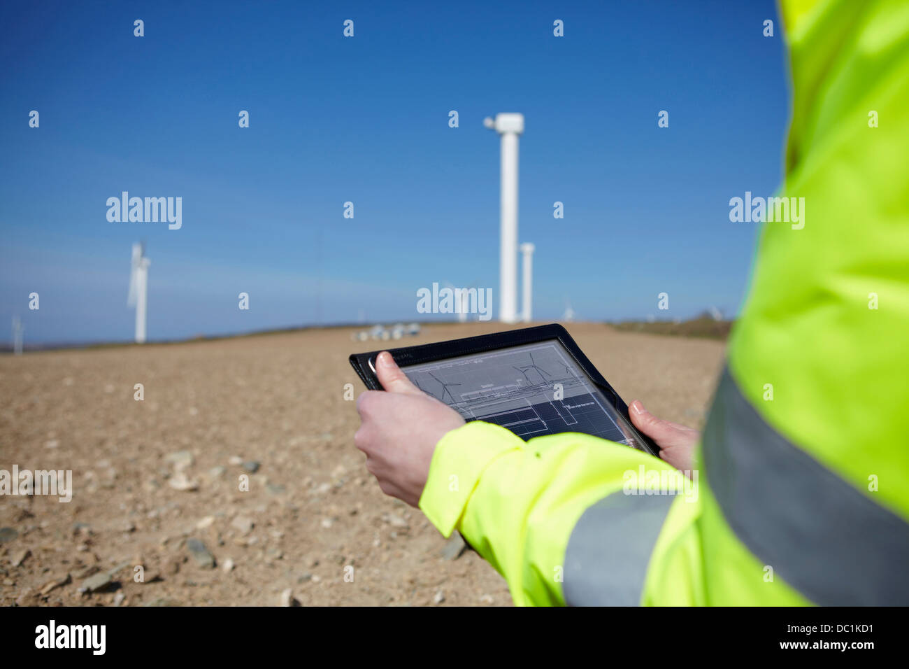 Project manager using digital tablet in front of wind farm - Stock Image