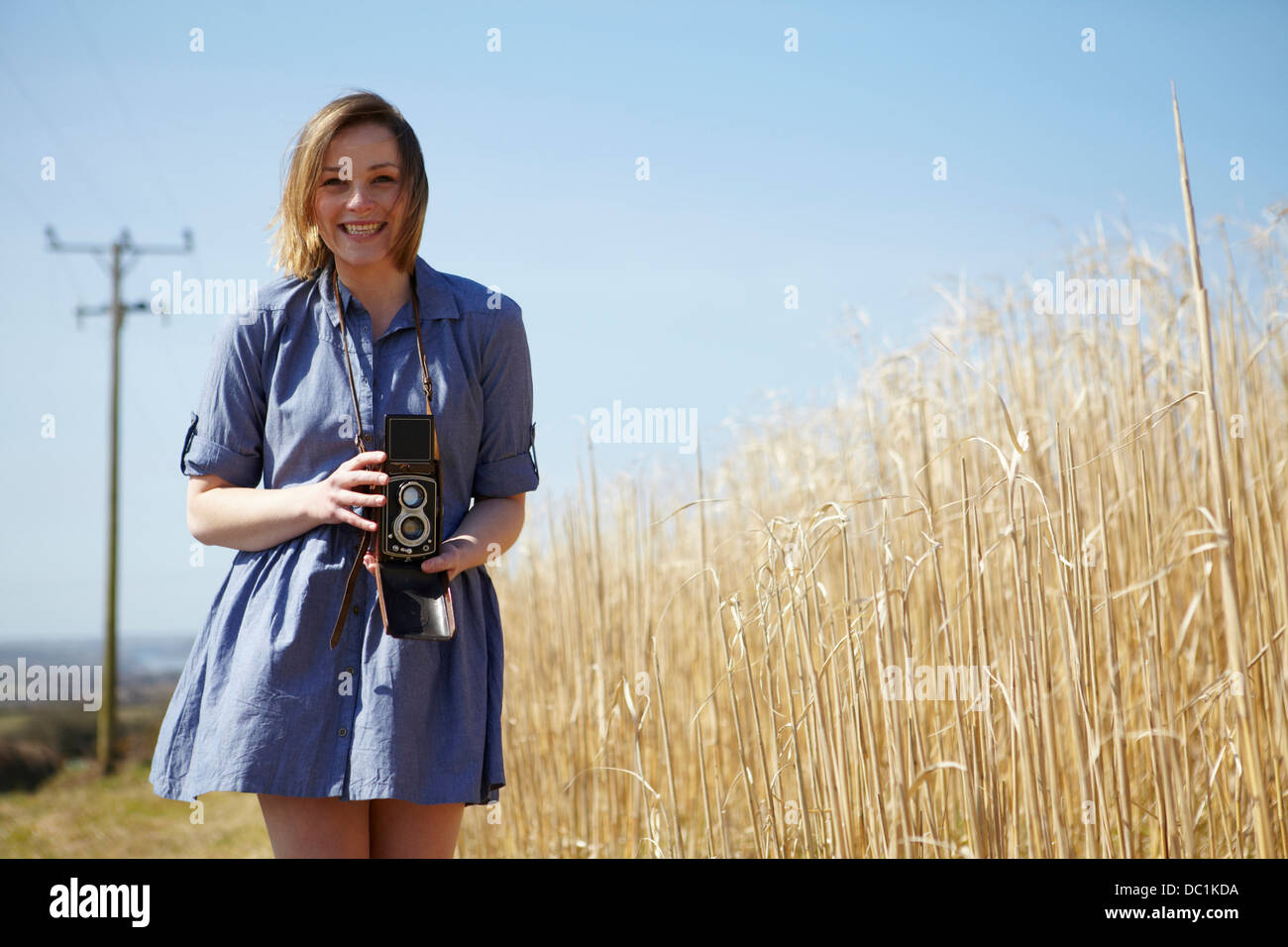 Portrait of young woman holding camera - Stock Image