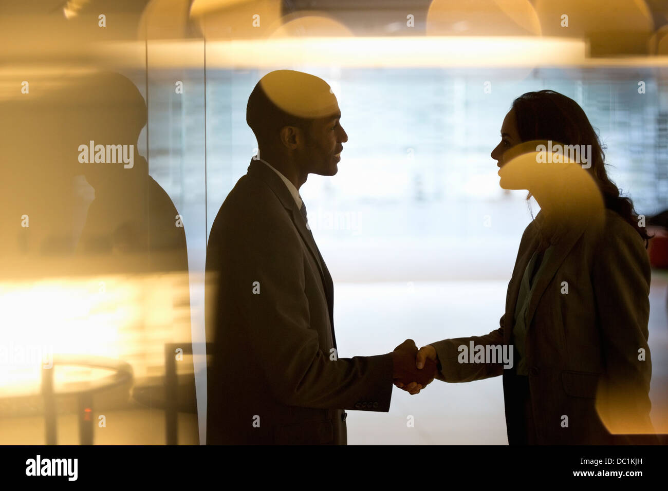 Businessman and businesswoman handshaking in lobby - Stock Image