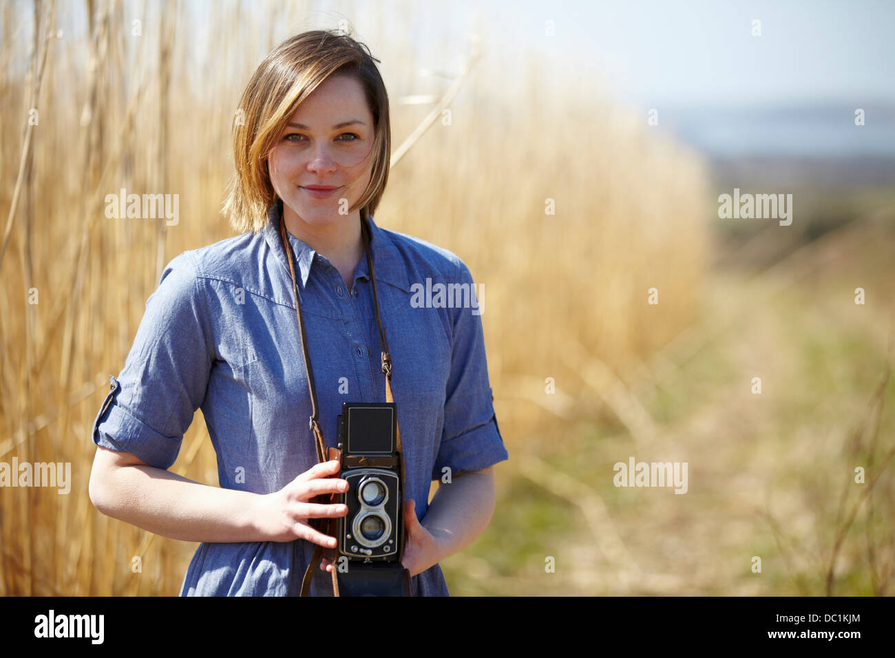 Close up portrait of young woman holding camera - Stock Image