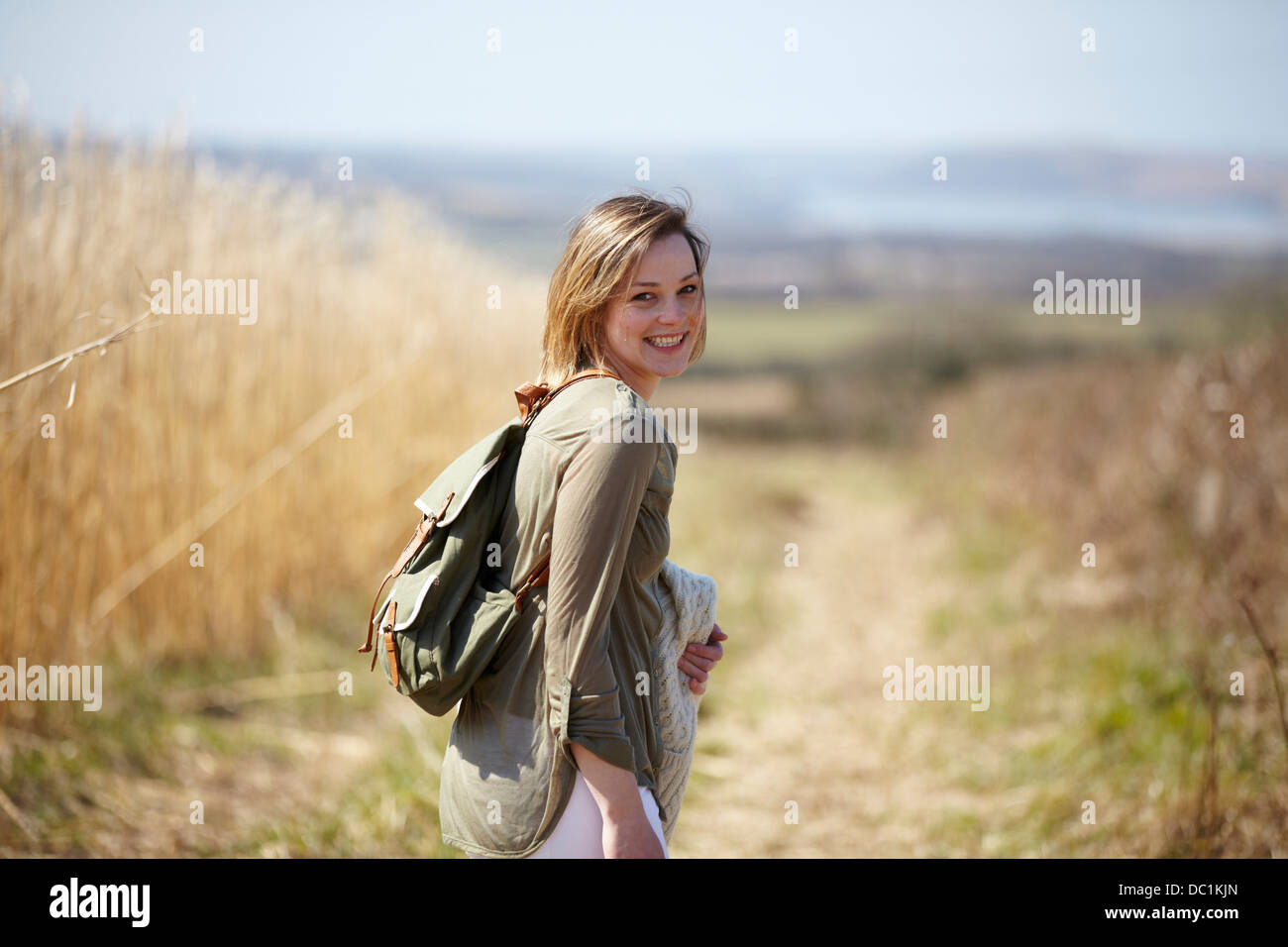 Portrait of young woman on dirt track next to field of reeds - Stock Image