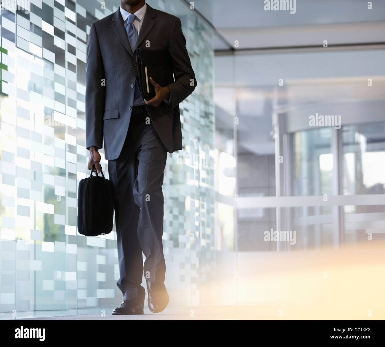 Businessman carrying briefcase in lobby - Stock Image