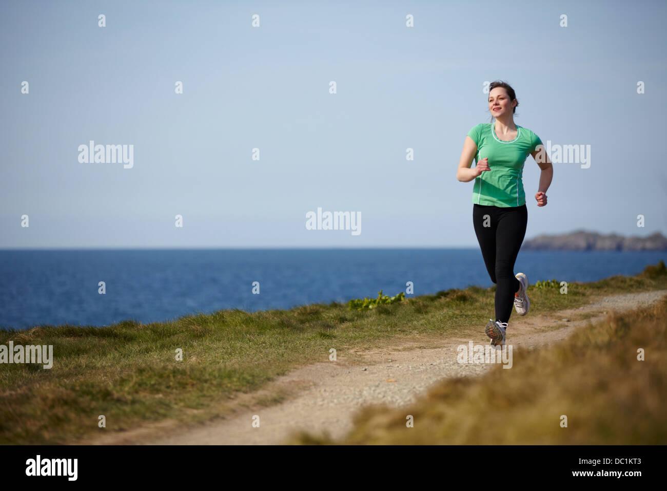 Young woman running along coastal path - Stock Image