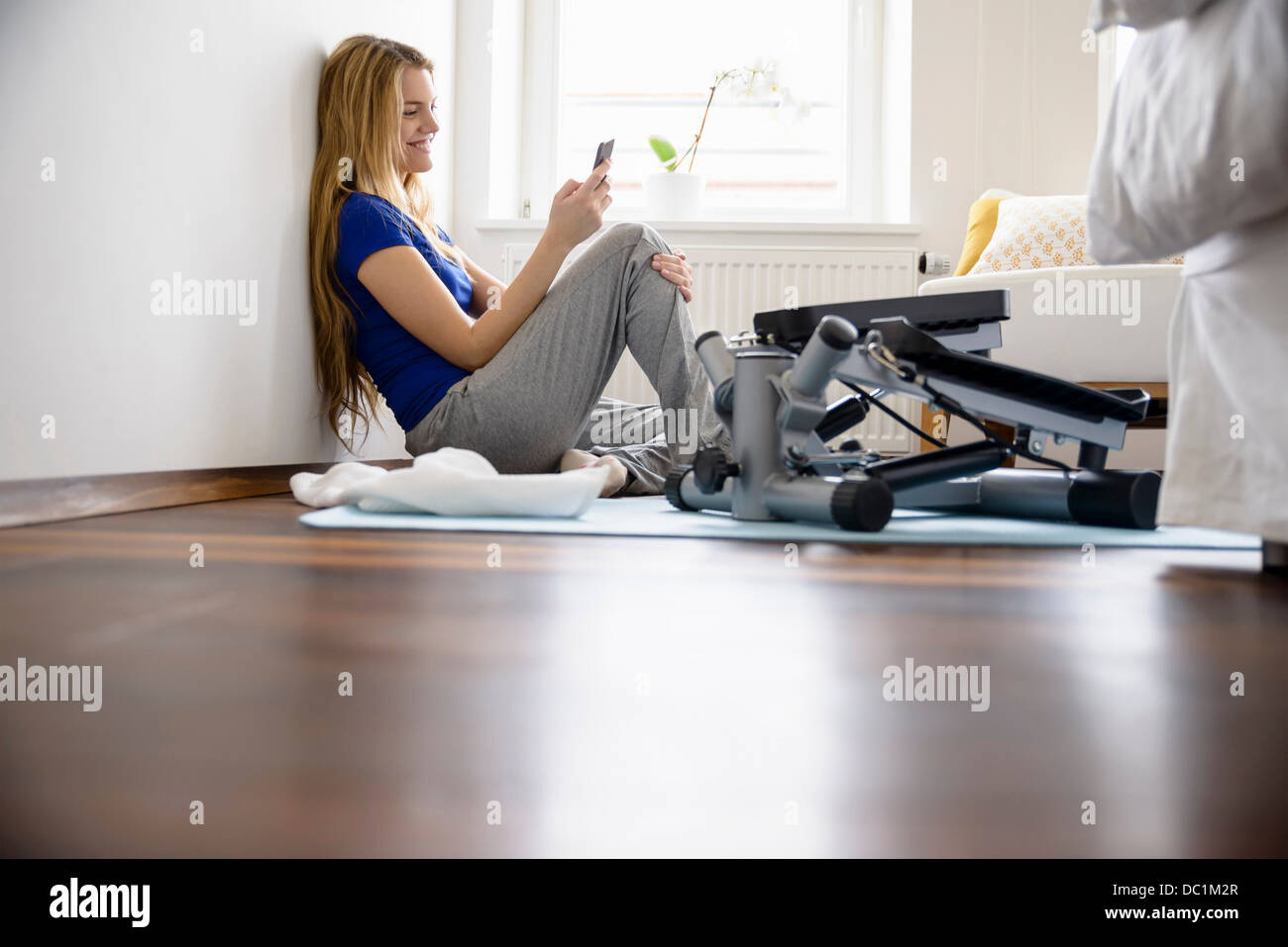Young woman sitting on bedroom floor looking at smartphone - Stock Image