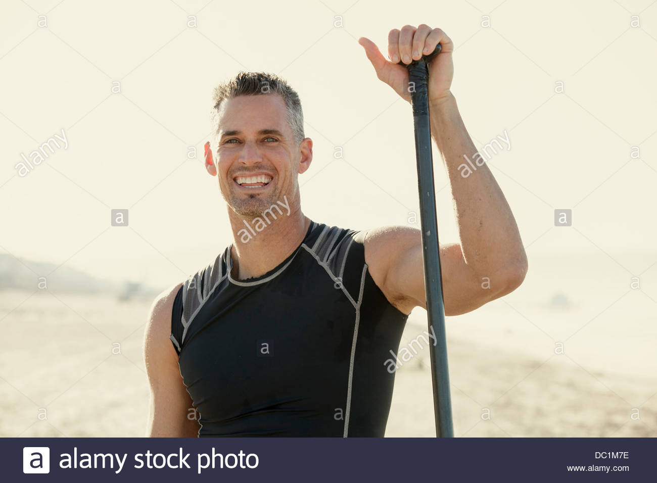 Mid adult man surfer standing with surf paddle on beach, portrait - Stock Image