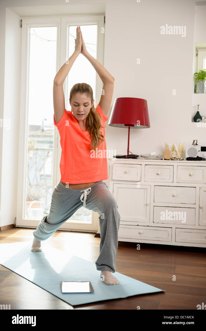 Young woman using digital tablet to aid exercise - Stock Image