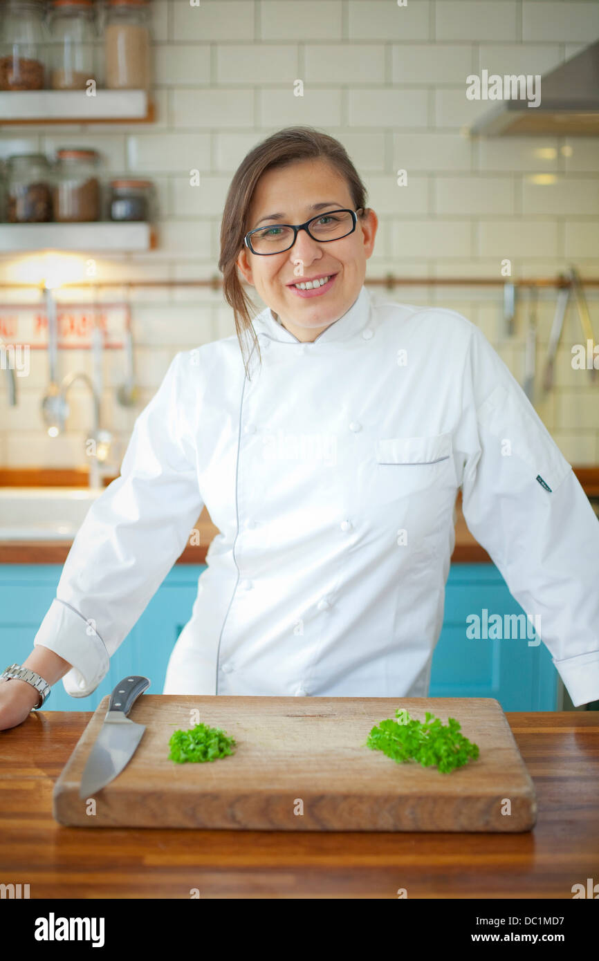 Portrait of female chef in commercial kitchen - Stock Image