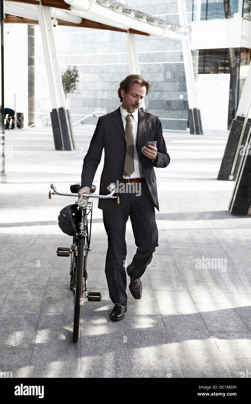 Mid adult businessman walking with bicycle and using mobile phone - Stock Image