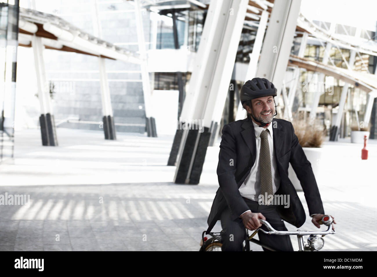 Mid adult businessman riding bicycle in city - Stock Image