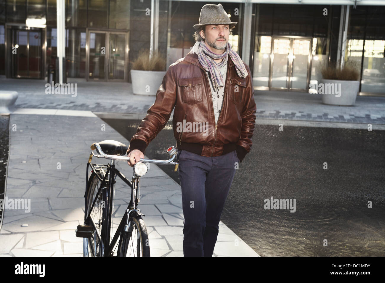 Mid adult man walking with bicycle in city - Stock Image