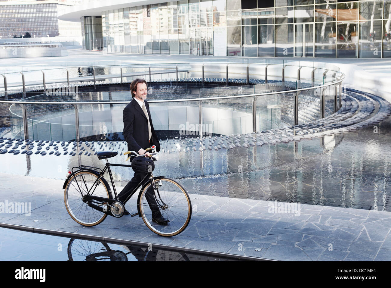 Mid adult businessman walking with bicycle by water feature in city - Stock Image