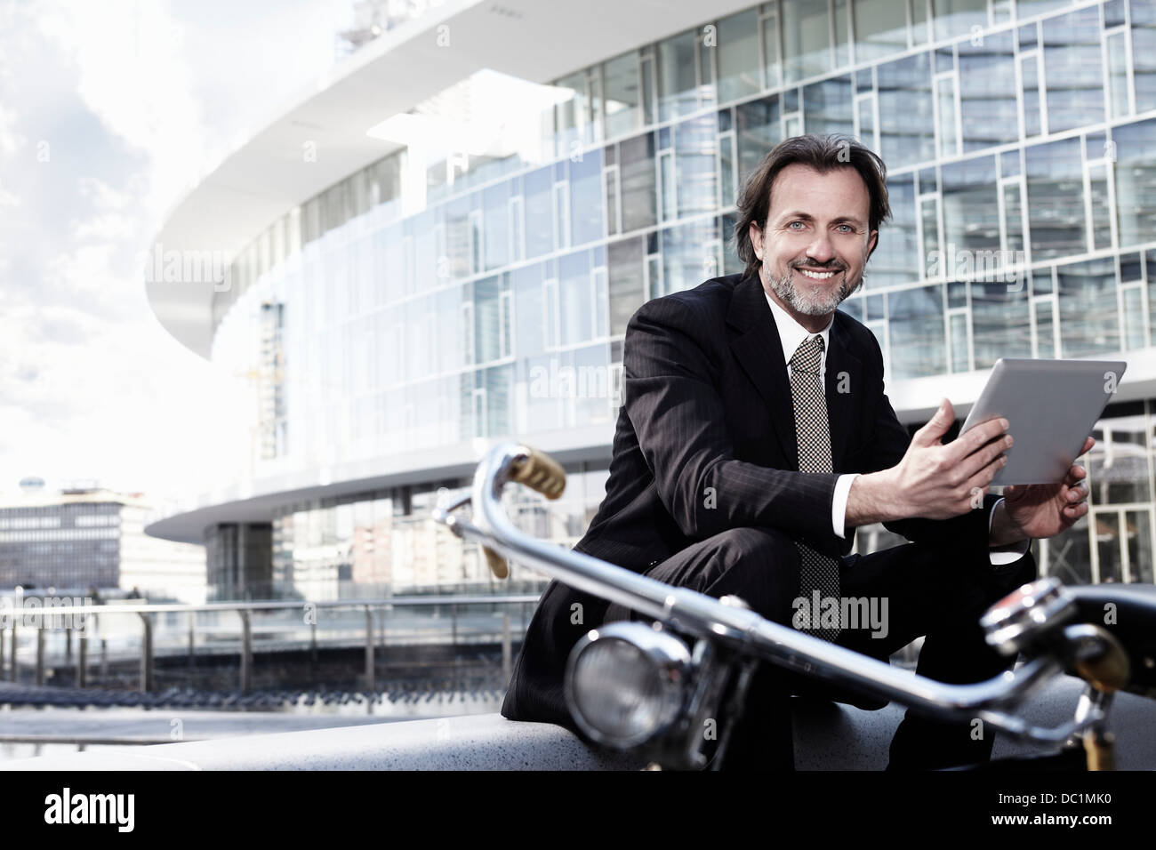 Mid adult businessman using digital tablet in city, portrait - Stock Image