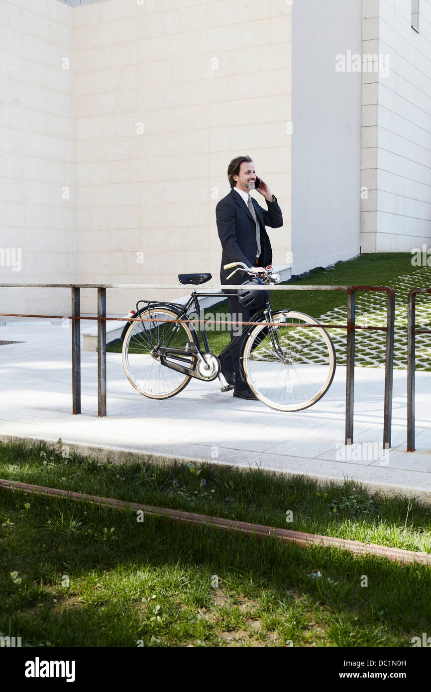 Mid adult businessman holding bicycle and using mobile phone - Stock Image