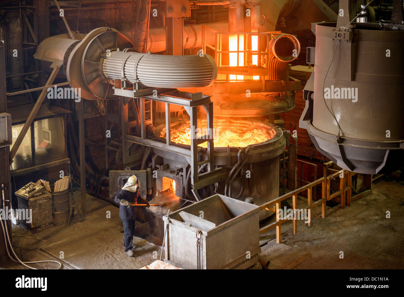 Elevated view of steel worker and furnace in steel foundry - Stock Image