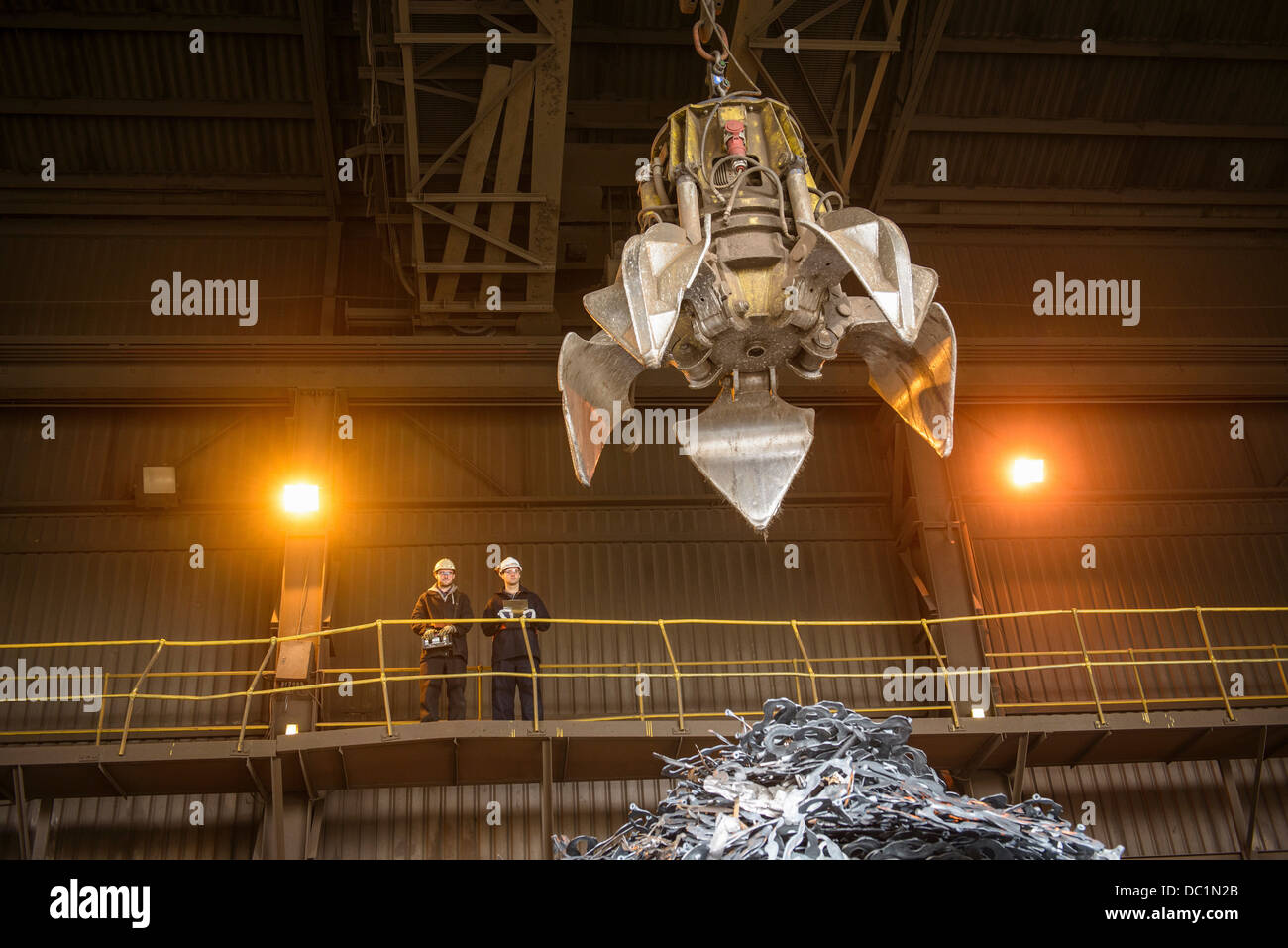 Steel workers overseeing mechanical grabber in steel foundry - Stock Image