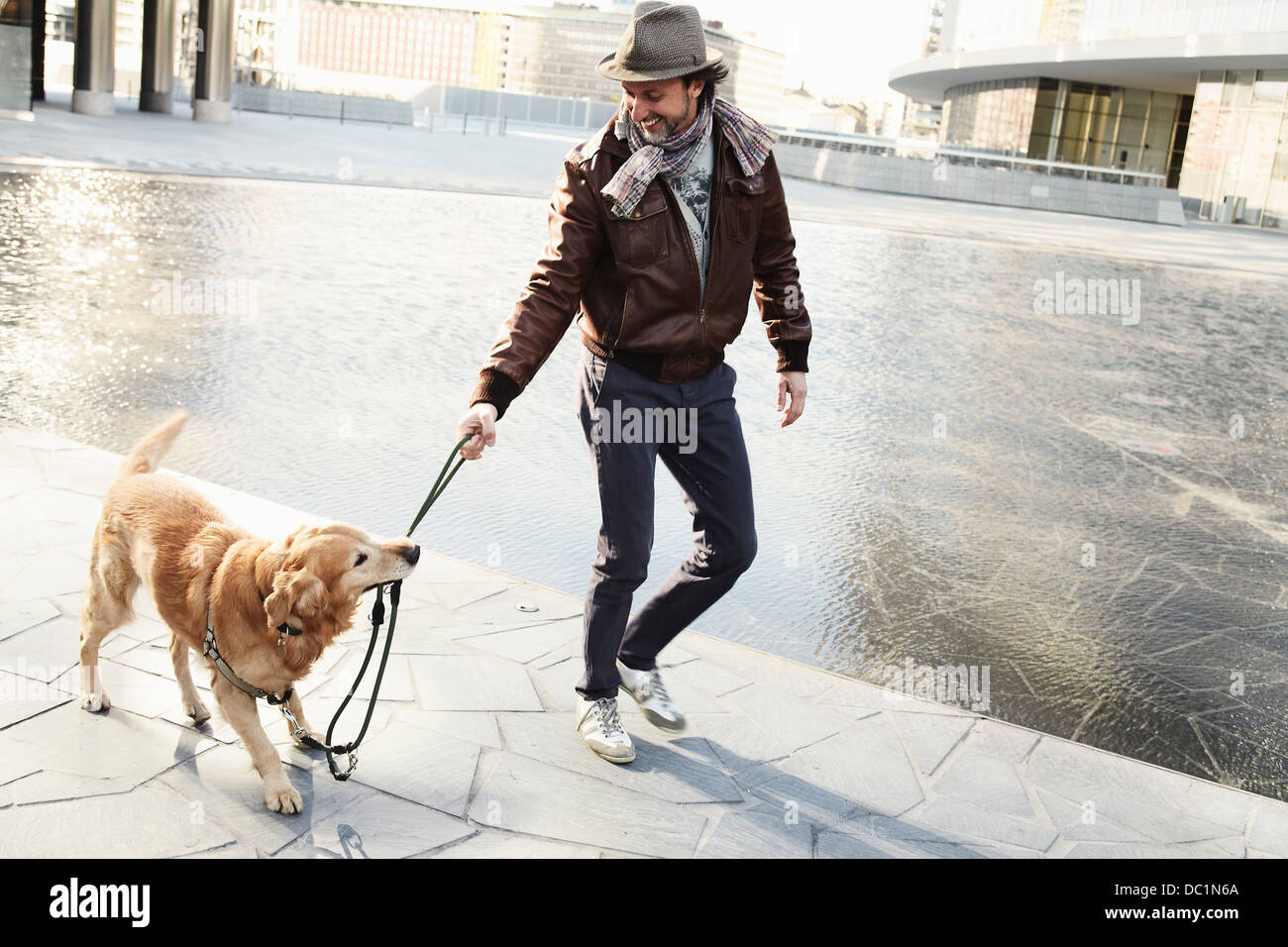 Mid adult man pulling leash on pet dog in city - Stock Image