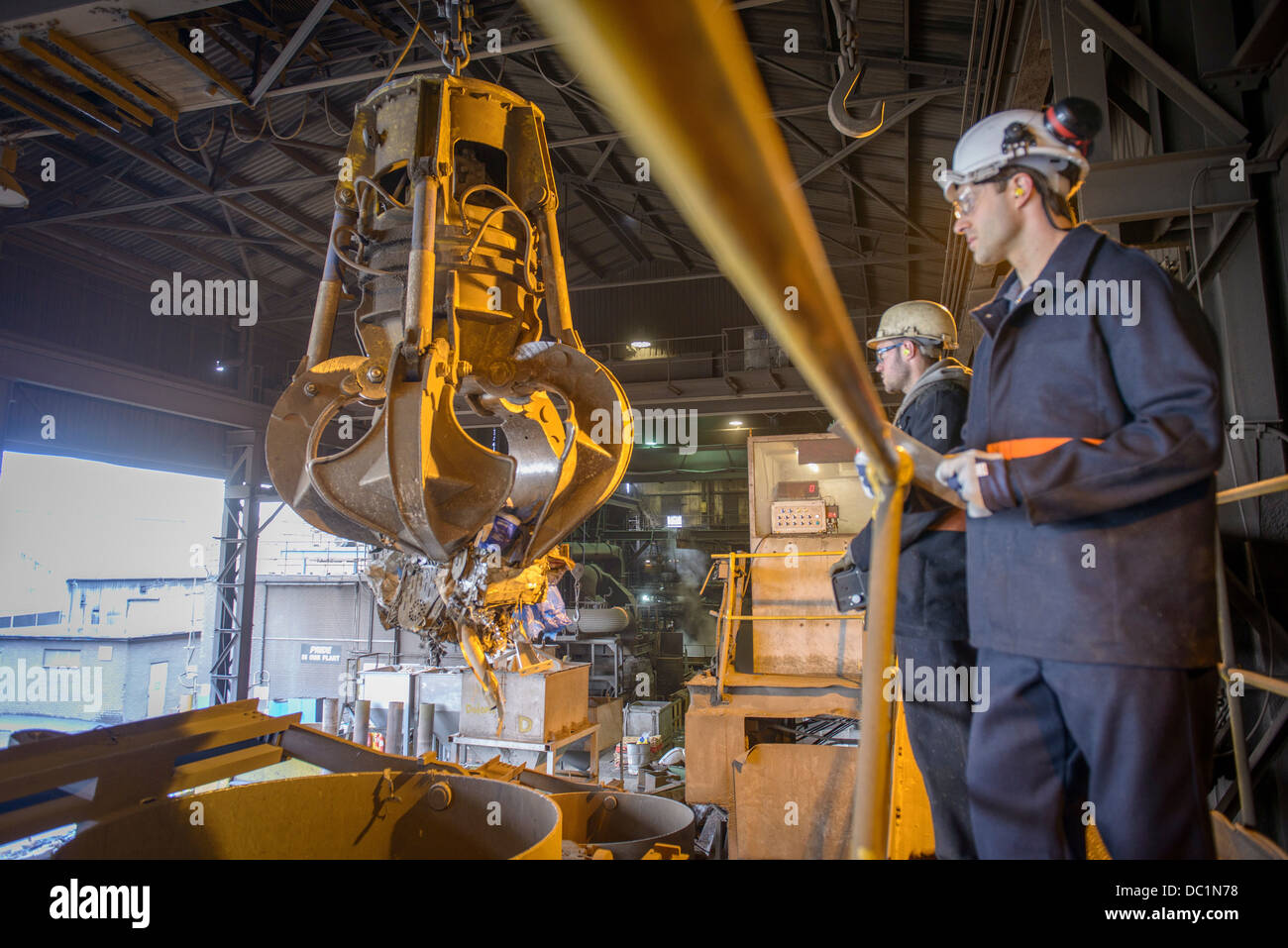 Workers watching mechanical grabber in steel foundry - Stock Image