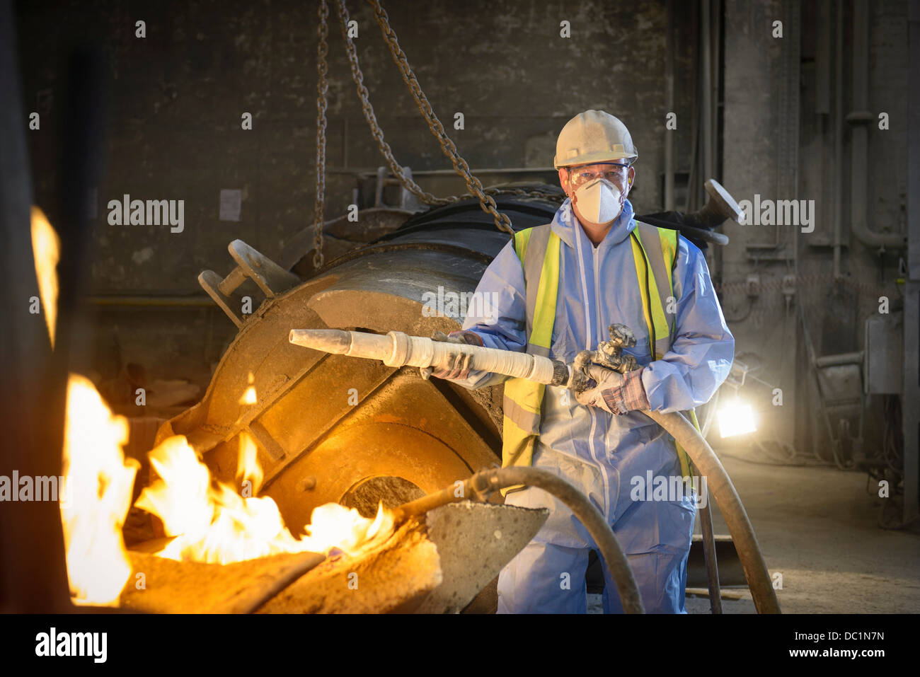 Portrait of steel worker holding industrial hose in steel foundry - Stock Image