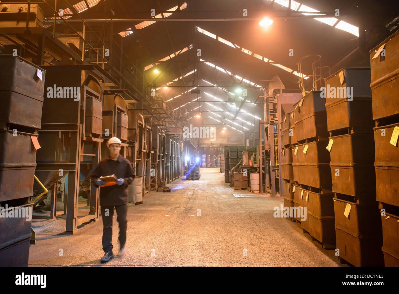 Worker walking past crates of steel shot in steel foundry - Stock Image