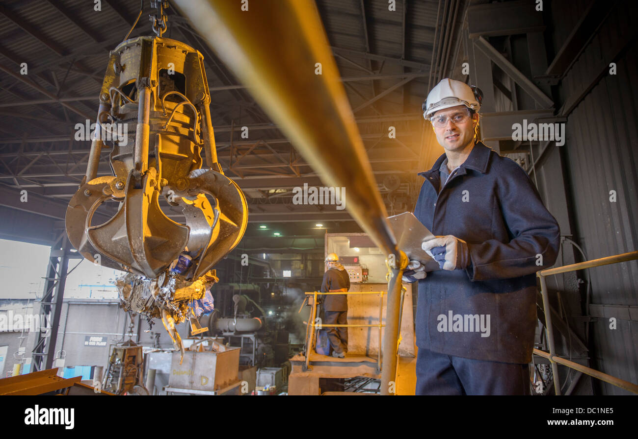 Portrait of steel worker overseeing mechanical grabber in steel foundry - Stock Image