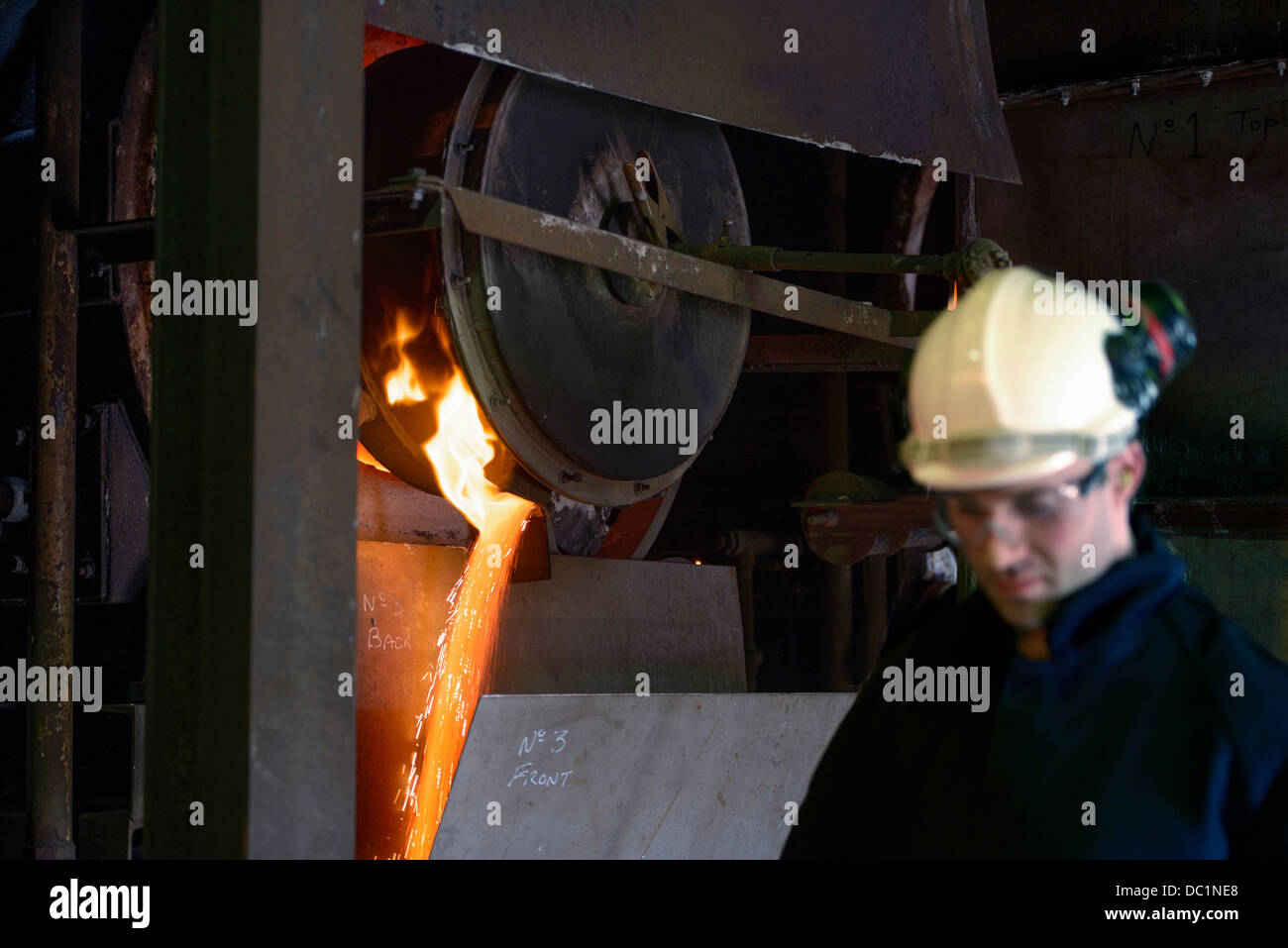 Steel worker in front of running molten metal in steel foundry Stock Photo