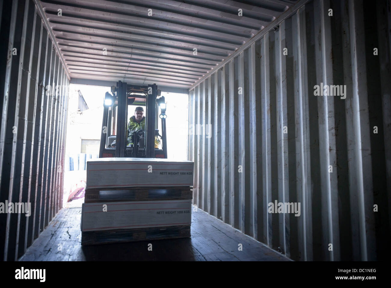 Fork lift truck loading boxes into container - Stock Image